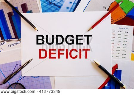 The Words Budget Deficit Is Written On A White Background Near Colored Graphs, Pens And Pencils. Bus