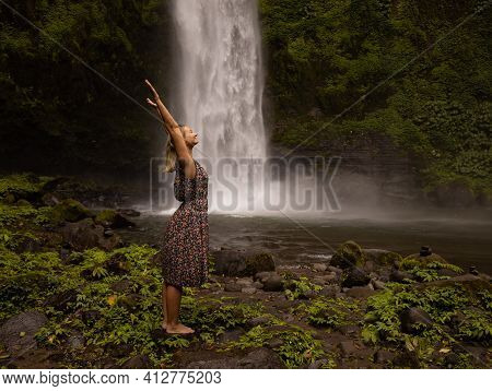 Happy Caucasian Woman Spending Time Near Waterfall, Raising Hands Up. Nature Concept. Energy Of Wate