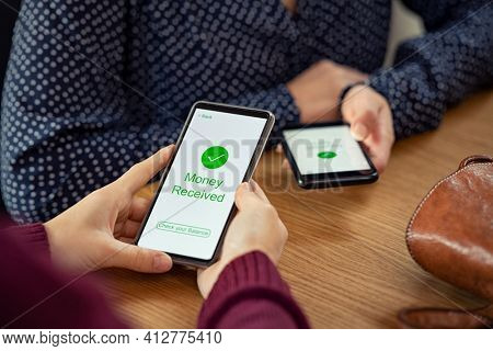 Close up of woman hands holding mobile phone with application to receive money. People holding smart phone and making cashless payment transaction. Smartphone screen displaying money received message.