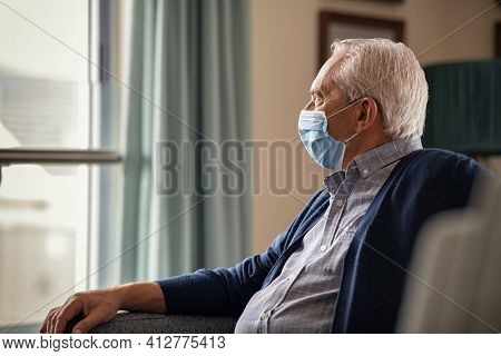 Lonely senior man with protective face mask sitting at home during covid-19. Depressed old man sitting on couch while wearing face mask for safety against coronavirus during quarantine at nursing home