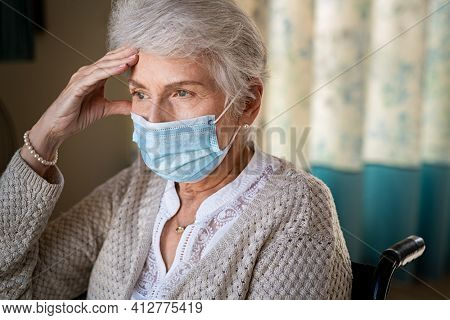 Portrait of lonely senior woman sitting in wheelchair wearing a face mask for safety against coronavirus. Disabled lady suffering from headache sitting at nursing home with protective face mask.