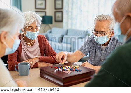 Group of seniors wearing protective face mask playing chinese checkers at nursing home during pandemic lockdown. Old man playing a board game wearing surgical mask for safety against covid-19.