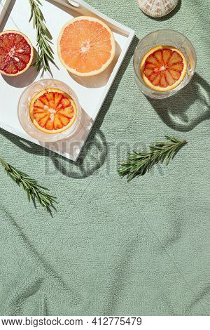 Summer Scene With Half Of Bloody Orange And Grapefruit,  Glasses Of Water And Rosemary With White Wo