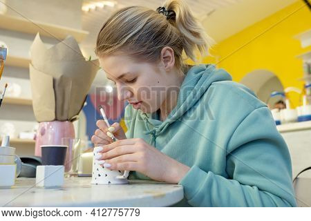 A Young Woman In Casual Clothes Draws On A Mug In A Ceramic Workshop. Learning New Skills, Improving