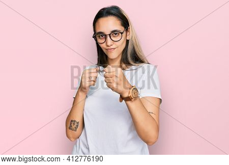 Young hispanic woman wearing casual white t shirt ready to fight with fist defense gesture, angry and upset face, afraid of problem