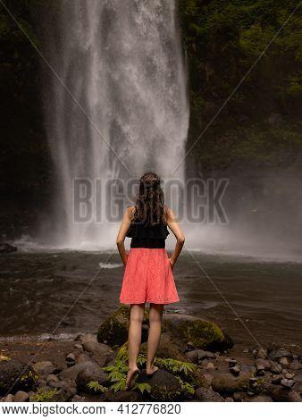 Traveler Woman Enjoying Waterfall Landscape. Caucasian Woman Wearing Pink Dress. Nature And Environm