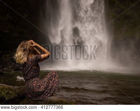 Young Caucasian Woman Sitting On The Rock And Enjoying Waterfall Landscape. Energy Of Water. Travel