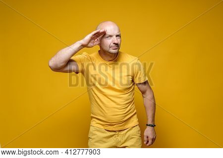 Bald Caucasian Man In A Yellow T-shirt Made A Strange Gesture, Put Hand To Head And Looks At The Cam