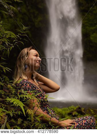 Young Caucasian Woman Enjoying Waterfall Landscape In Tropical Forest. Woman Portrait. Energy Of Wat