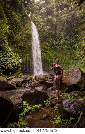 Caucasian Woman Traveller Enjoying Waterfall Landscape In Tropical Forest. Energy Of Water. Travel L