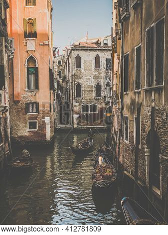 Venice, Italy, February 19, 2021, Two Gondoliers driving a gondola with a family of tourists in a small canal street in Venice