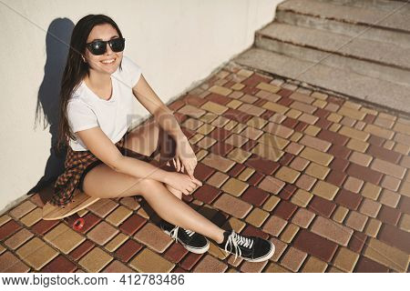 Cheerful And Carefree Brunette Girl In Hipster Outfit, Skater Sneakers Smiling Joyfully Gazing Eveni