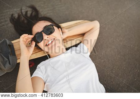 Urban Lifestyle And Skateboarding Concept. Upper View Smiling Girl In Sunglasses Lying On Concrete A