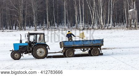 Huntsman On A Tractor With A Trailer Throws Out Top Dressing For Wild Animals In Winter. Laying Out