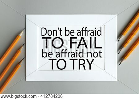 Don't Be Afraid To Fail, Be Afraid Not To Try. Text On White Paper In White Frame On Gray Background