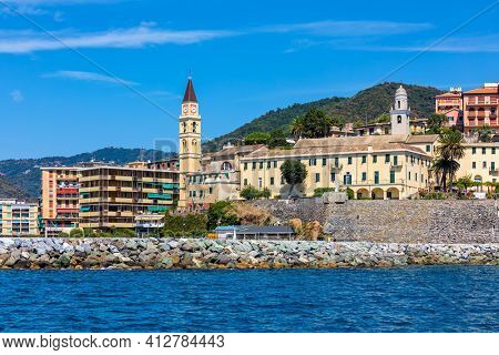 View from the sea on houses and belfry under blue sky in small town of Recco in Liguria, Italy.