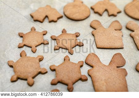 Baked Gingerbread Cookies In Various Shapes Without Decorations, Lying On Baking Paper.