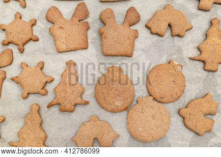 Baked Gingerbread Cookies In Various Shapes Without Decorations, Lying On Baking Paper, Top View.