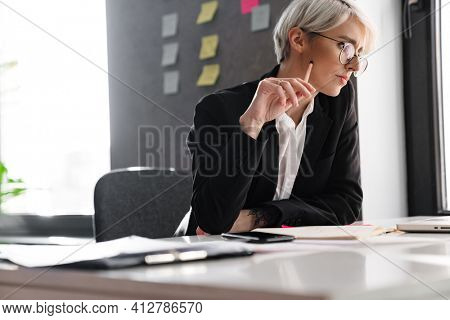 White-haired puzzled woman working with laptop while sitting at table in office
