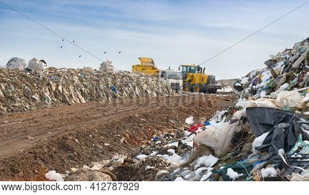 Dump Truck Unloading Garbage Over Vast Landfill.  Environmental Pollution. Outdated Method Of Waste