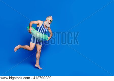 Full Size Profile Side Photo Of Mature Smiling Man With Buoy Jumping In Pool Isolated On Blue Color