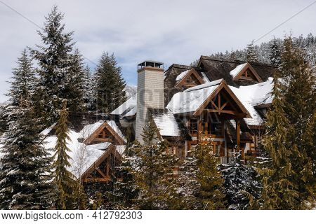 Chalets And Vacation Homes In A Village At A Famous Ski Resort With Mountains Landscape In Backgroun