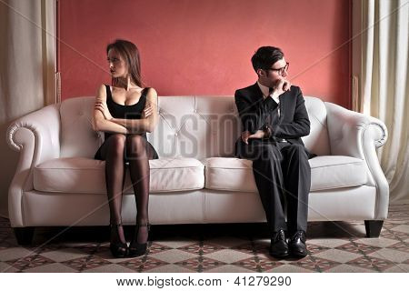 A woman and a man sitting on white sofa are turned on the opposite side
