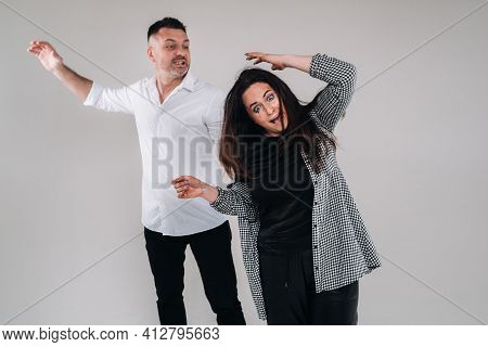 A Man Swings His Fist At A Battered Woman Standing On A Gray Background. Domestic Violence