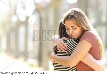 Regretful Woman Embracing A Friend Reconciliating In The Street
