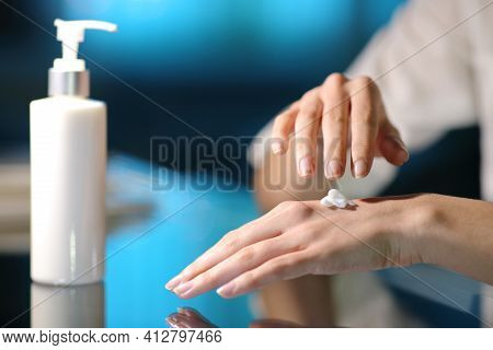 Close Up Of A Woman Hands Rubbing Moisturizer Cream In The Night At Home