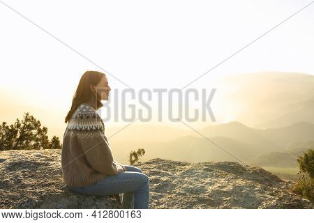 Side View Portrait Of A Casual Woman In The Top Of A Cliff Contemplating Views In Winter