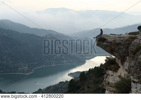 Full Body Portrait Of A Sad Woman Complaining Sitting In The Top Of A Cliff In The Mountain
