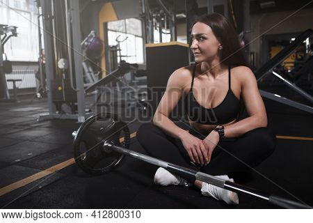 Attractive Sportswoman Resting After Barbell Weightlifting Workout At Sports Studio