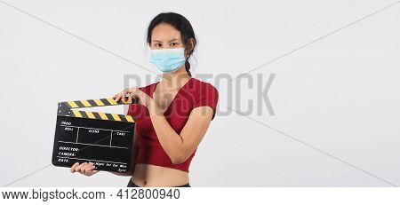 Woman Wear Face Mask And Hand's Holding Black Clapper Board Or Movie Slate Use In Video Production ,