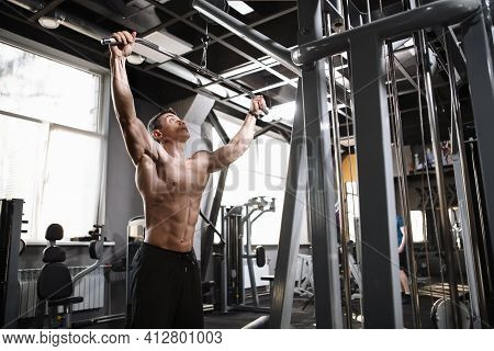Low Angle Shot Of A Ripped Strong Male Bodybuilder Exercising On Lat Pull Down Gym Machine