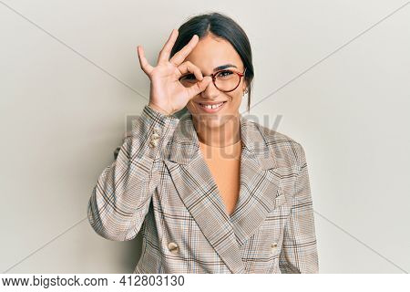 Young brunette woman wearing business jacket and glasses doing ok gesture with hand smiling, eye looking through fingers with happy face.