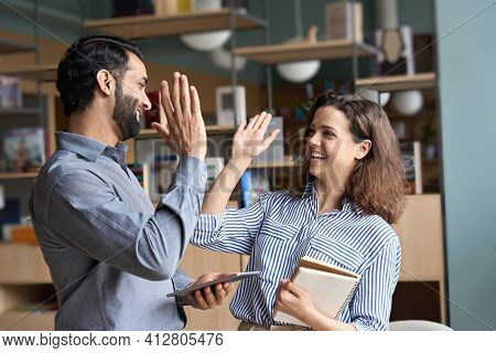 Two Happy Friendly Diverse Professionals, Teacher And Student Giving High Five Standing In Office Ce
