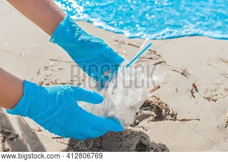 The Girl's Hands In Blue Protective Home Gloves Remove Garbage On The Sea Shore Near The Water Close