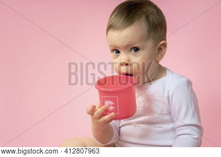 Portrait Of A Small Child Biting His Toy. Close Up Baby Toddler Girl, Close-up Toddler Girl On A Sol