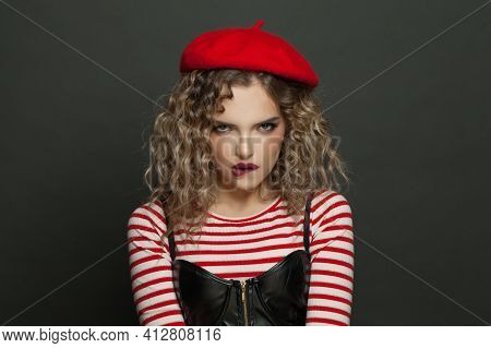 Portrait Of Young Funny Woman In Red French Style Beret Scowling On Black Wall Background