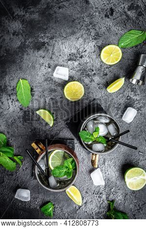 Flat-lay Of Lime Moscow Mule Alcohol Cocktails With Fresh Mint And Ice In Copper Mugs On Dark Backgr