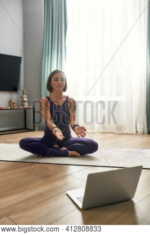 Young Girl Trainer Siting Relaxing On A Sports Mat And Meditates. Young Girl In Sportswear Exercisin