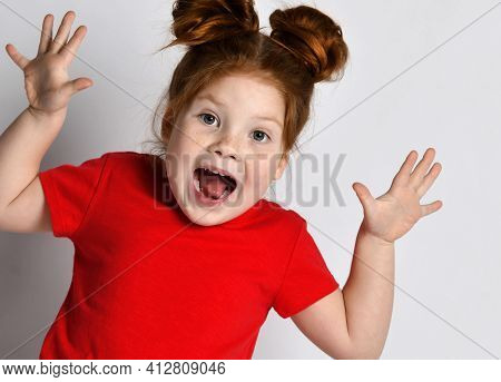 Child Screams Loudly. Stylish Little Girl With Freckles And Red Hair Screams With Her Mouth Wide Ope