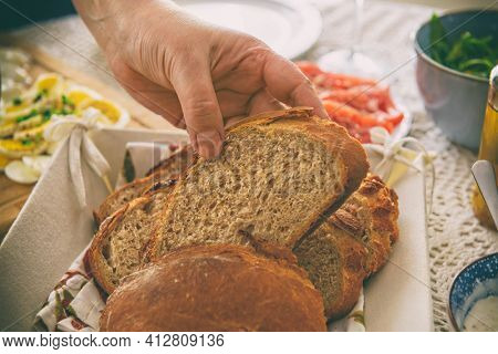 A loaf of bread cut into slices in a hand. A continental, healthy breakfast containing homemade bread. Bread based on spelt and rye flour with the addition of wheat flour