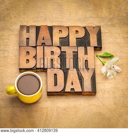 Happy Birthday greeting card in vintage letterpress wood type with coffee against handmade bark paper