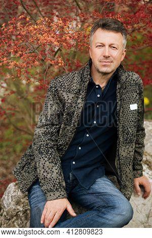 Portrait of handsome mature man posing in spring park
