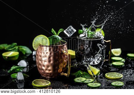 Moscow Mule Cocktail With Lime, Mint And Cucumber Splashes And Ice Frozen Motion.