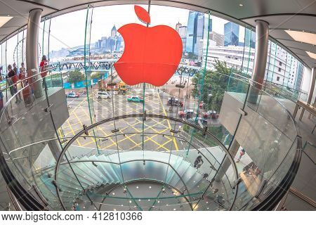 Hong Kong, China - December 4, 2016: Fish-eye Wide View Of Red Apple Sign And Modern Spiral Staircas