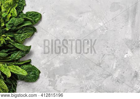 Green Fresh Spinach Leaves On A Neutral Gray Background. Top View With Copy Space For Text. Healthy