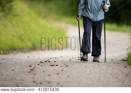 Senior person staying fit by doing daily cardio exercise, going for a fast paced power walk with sticks